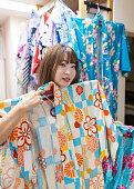 Young woman choosing yukata in rental store