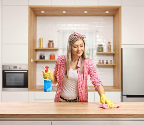 junge frau putzt eine holztheke in einer küche - backofenfenster reinigen stock-fotos und bilder
