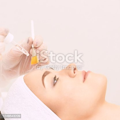 Young woman cleaning face skin in salon. Retinol peel with brush. Acid organic peeling.