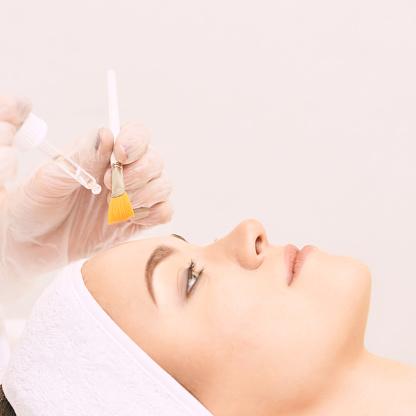 Young woman cleaning face skin in salon. Retinol peel with brush. Acid organic peeling.