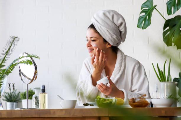 Junge Frau putzt Gesicht mit Naturkosmetik – Foto