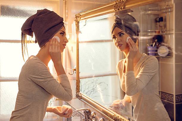 若い女性クリーニングしない彼女の顔のバスルームを完備。 ストックフォト