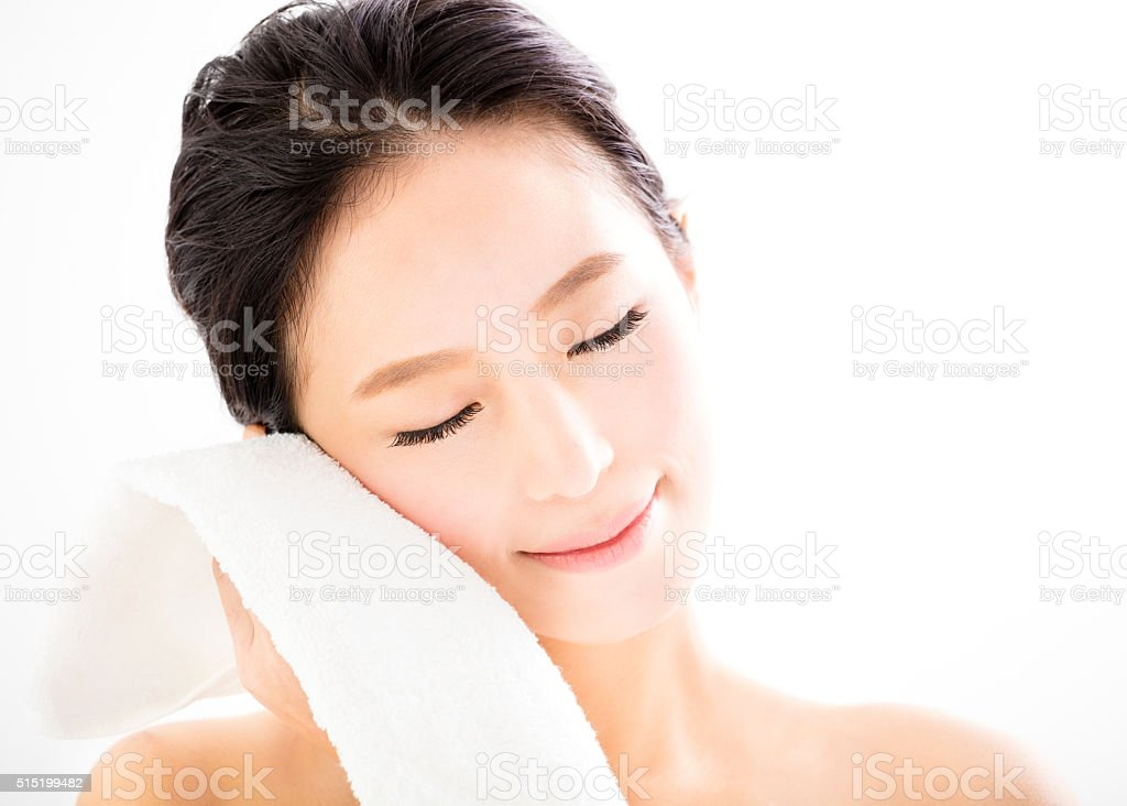 young woman cleaning her face with  towel stock photo