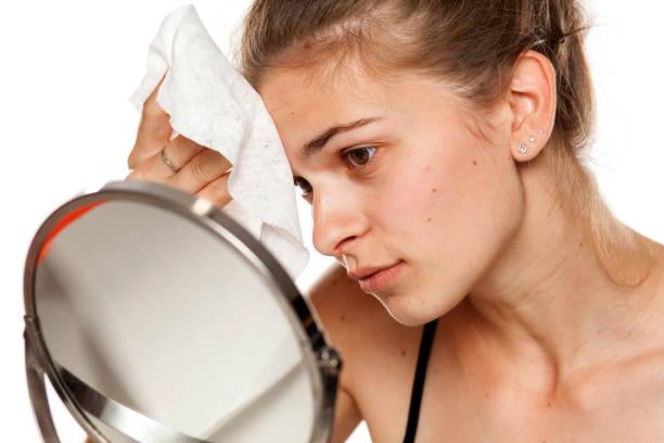 若い女性の白い背景にウェットティッシュで顔を洗浄 ストックフォト