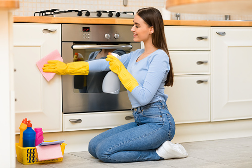 Young woman cleaning kitchen furniture using sprayer
