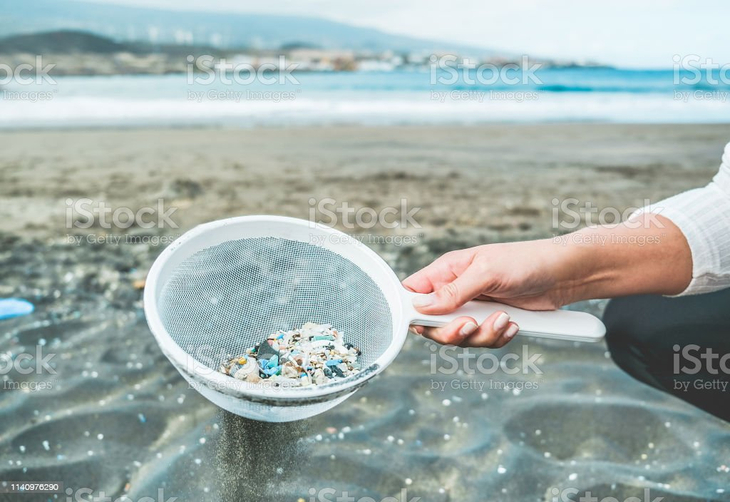 Young woman cleaning microplastics from sand on the beach - Environmental problem, pollution and ecolosystem warning concept - Focus on hand - Foto stock royalty-free di Accudire