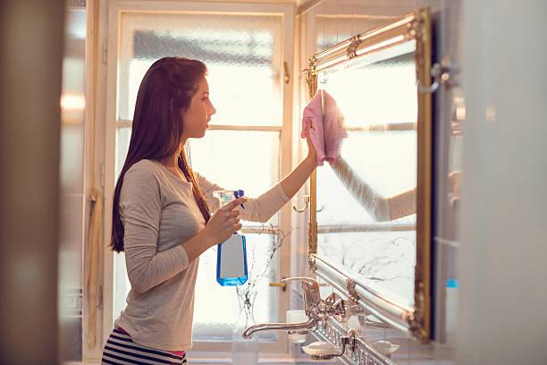 Jeune femme nettoyage, miroir dans la salle de bains. - Photo