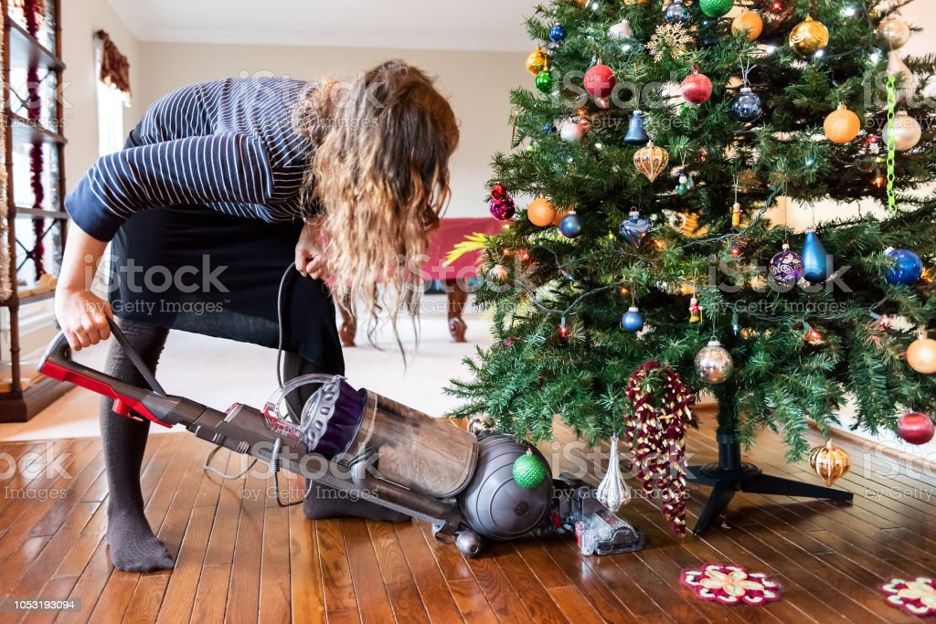 Young woman cleaning with vacuum cleaner, vacuuming under Christmas Tree needles with New Years ornaments on hardwood wooden floor stock photo