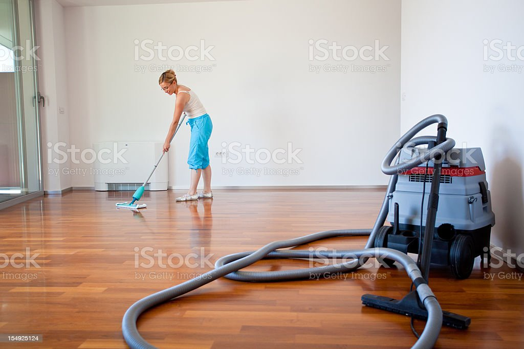 Young woman cleaning wooden floor stock photo