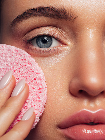 Young woman cleans the skin natural sponge