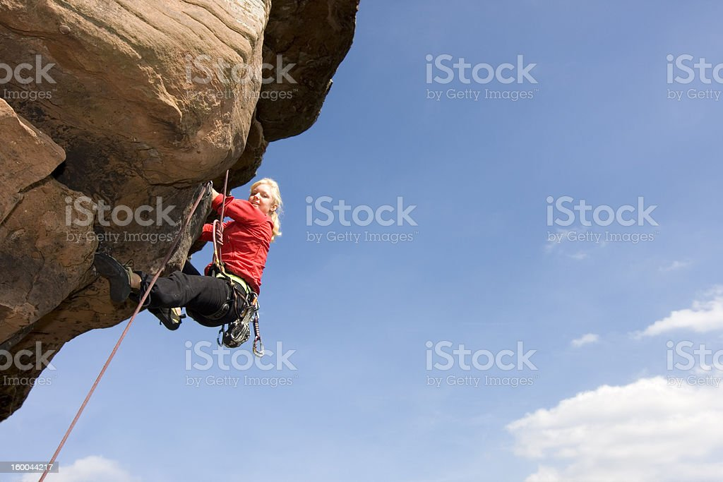 Young woman climbing a rock royalty-free stock photo
