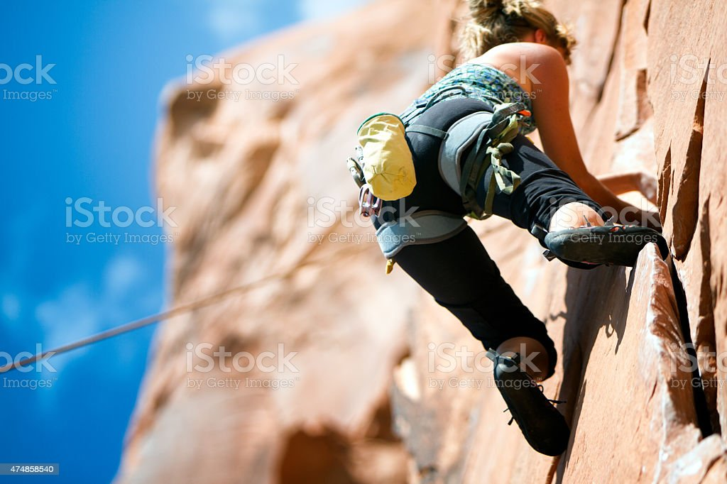 Young woman Climbing a Sandstone Cliff  Near Moab Utah stock photo