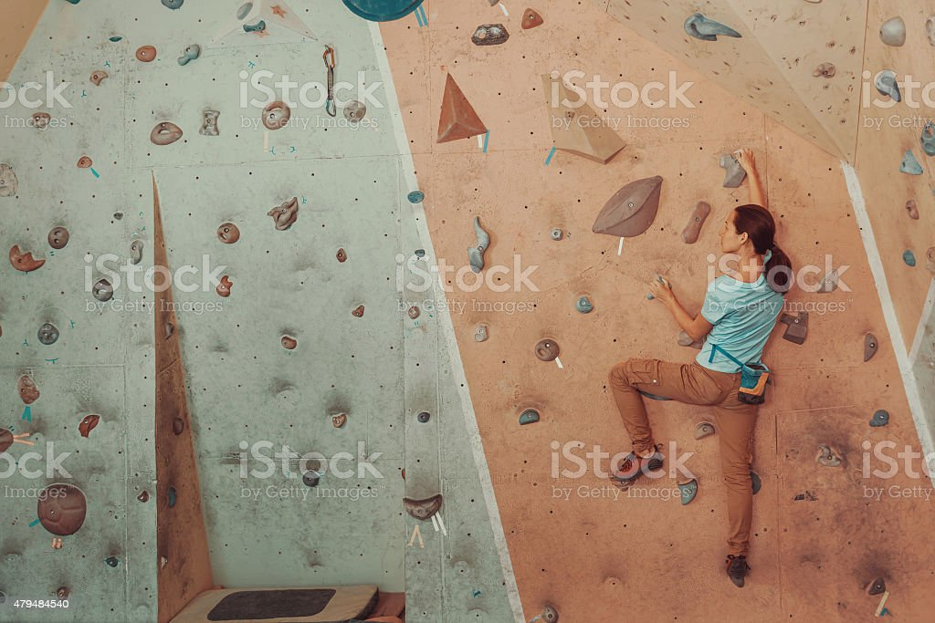 Young woman climbing artificial boulder in gym stock photo