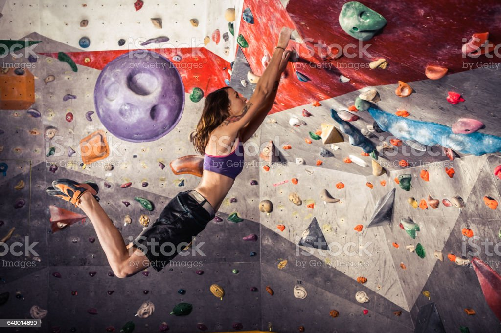 young woman climbing artificial boulder indoors stock photo