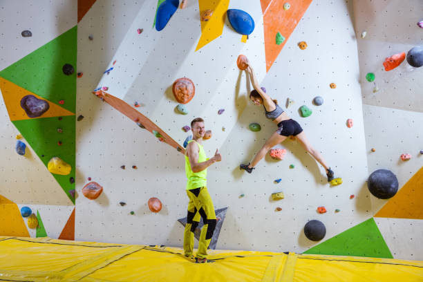 Young woman climbing bouldering problem (route), male instructor showing thumb up stock photo