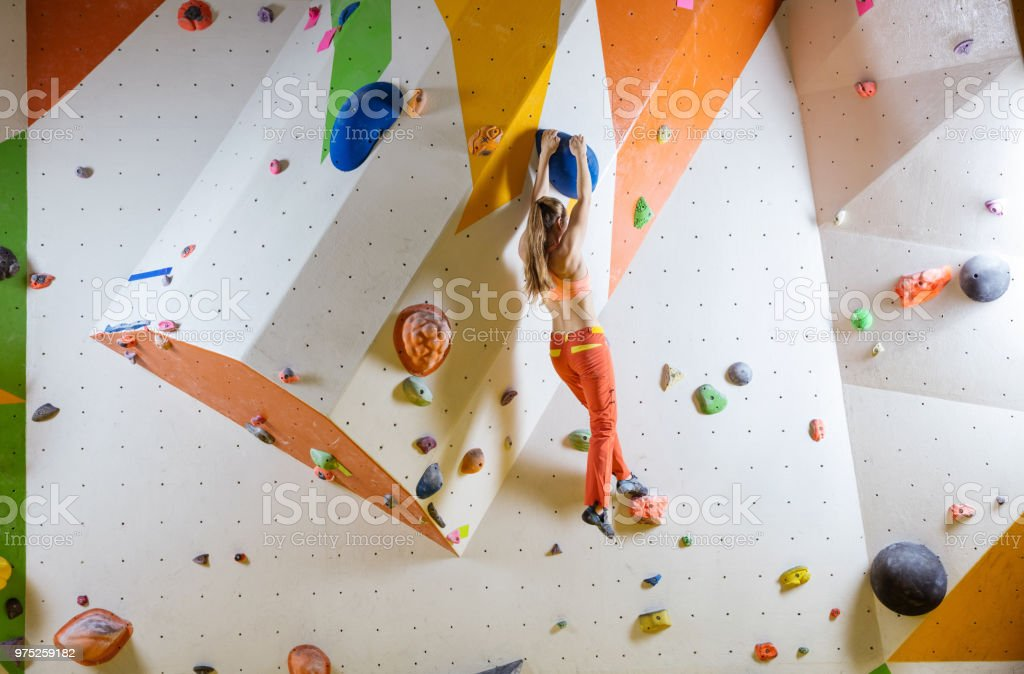 Young woman climbing bouldering route stock photo
