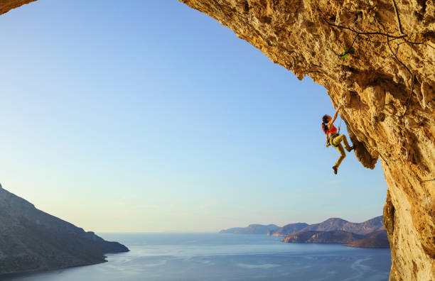 Young woman climbing challenging route in cave stock photo