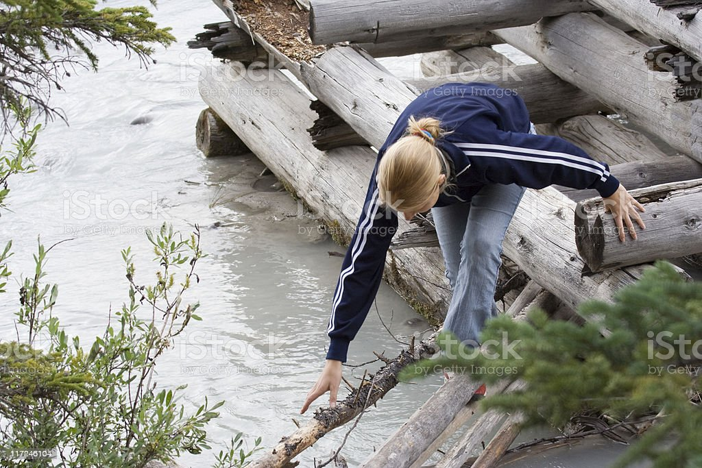 young woman climbing on a wooden raft royalty-free stock photo