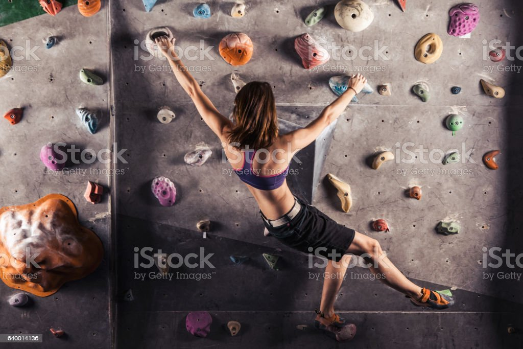 Young woman climbing up on practice wall – Foto