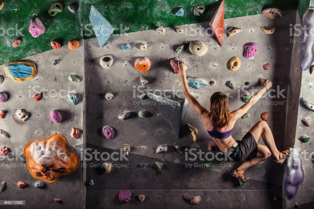Junge Frau klettert auf Übungswand – Foto
