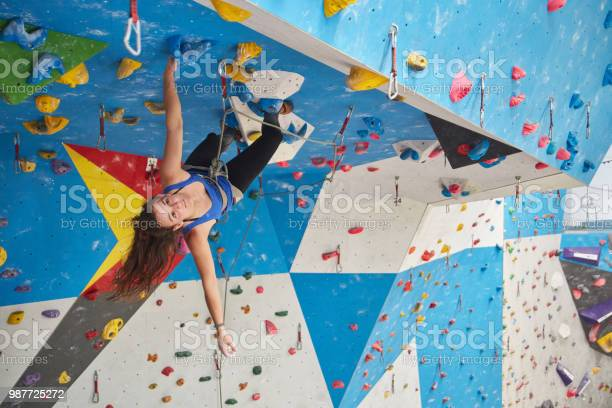 Young woman climbing wall in gym. Full length of determined female is exercising. She is in sports clothing.