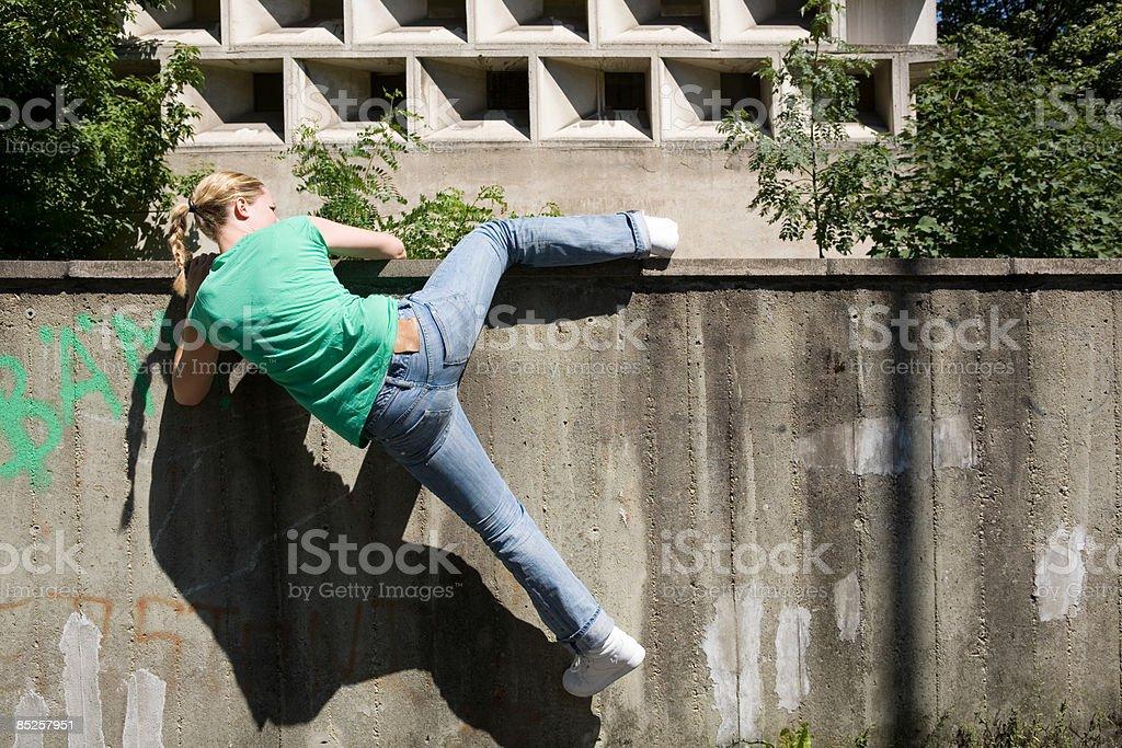 Young woman climbing wall royalty-free stock photo