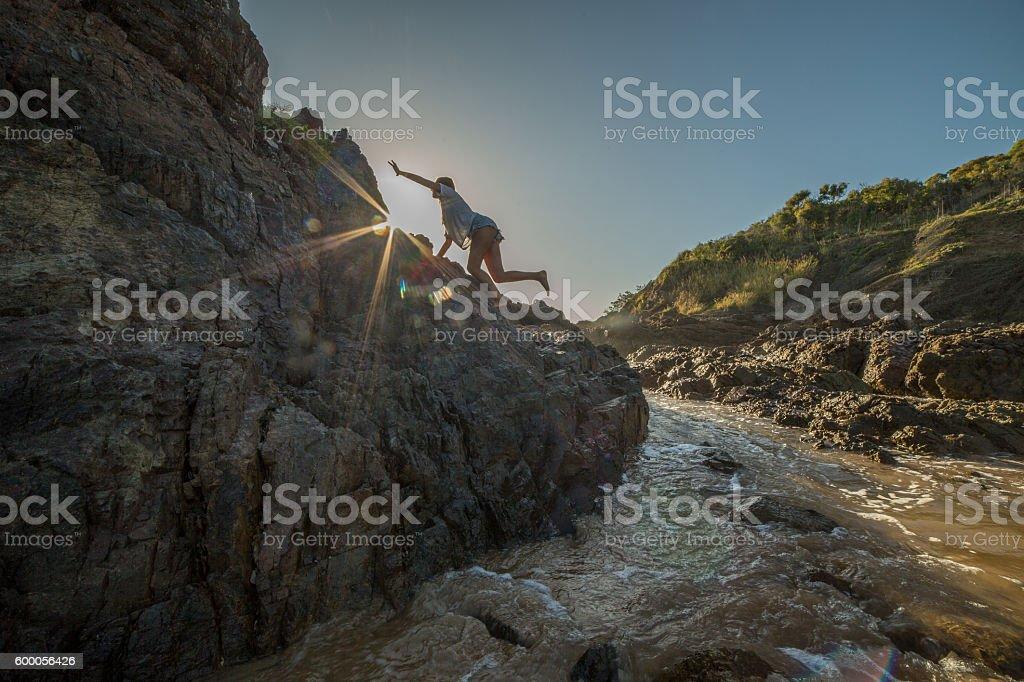 Young woman climbs steep rock, towards sunlight stock photo