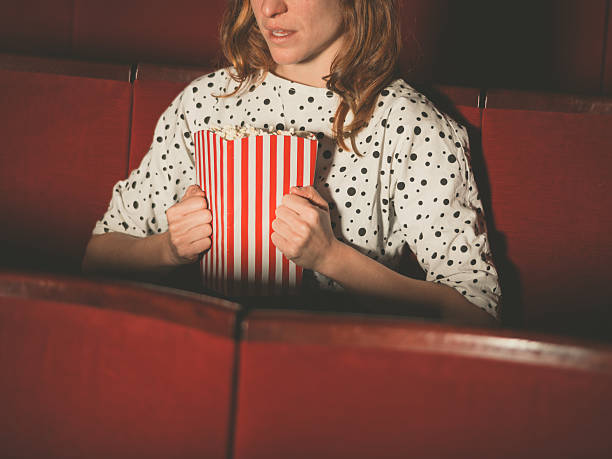 junge frau bahnt popocorn in kino - rot bekümmerte möbel stock-fotos und bilder