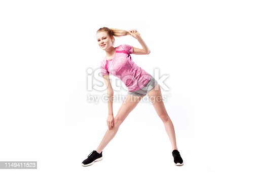 Sporty woman in t-shirt and shorts smilling and tilts to the leg, legs apart shoulder-width apart  on white isolated  background. Photo of muscular woman in sportswear on white background. Strength and motivation.