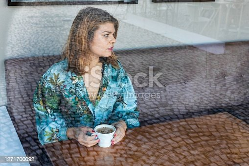 Portrait of a young woman sitting at the cafe and enjoying cup of coffee. The coffee bar is next to the train station of Lisbon, Portugal. Is a place with wooden tables and fresh tasty food