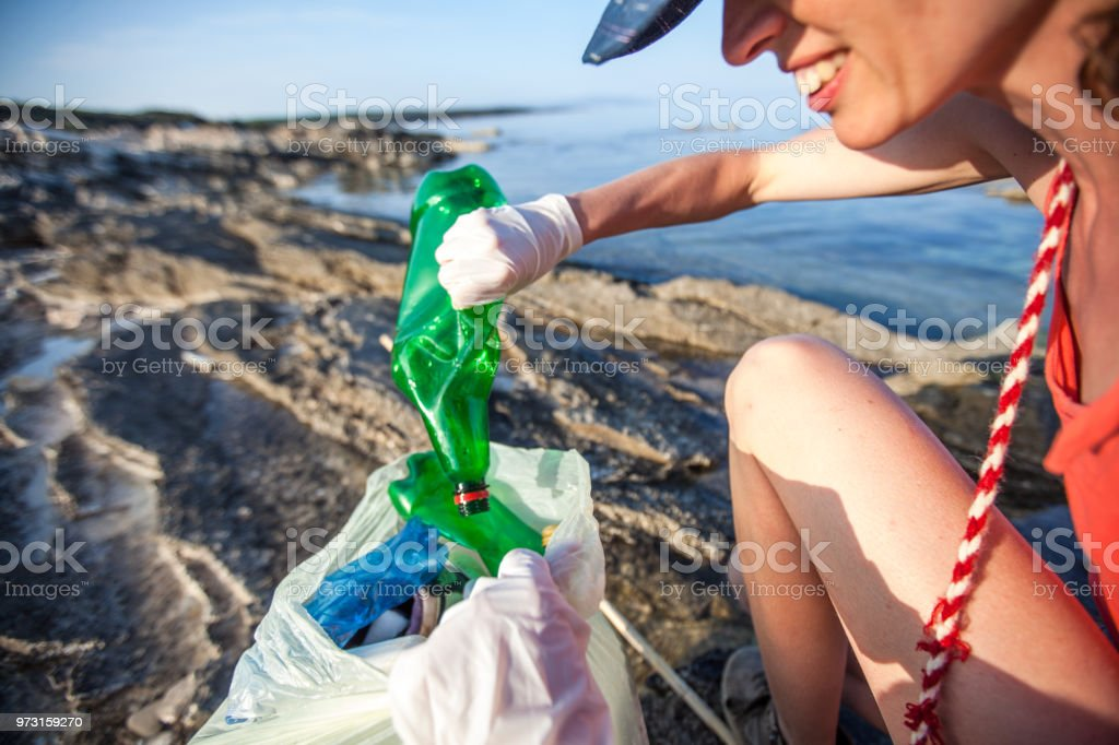 Young Woman Collecting Litter on Seashore stock photo