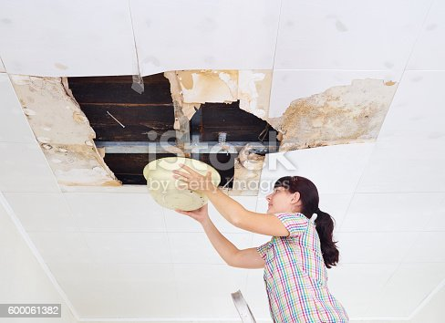 istock Young Woman Collecting Water In basin From Ceiling. Ceiling pane 600061382