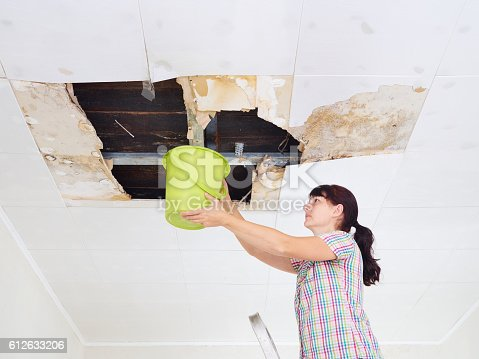 istock Young Woman Collecting Water In Bucket From Ceiling. Ceiling pan 612633206