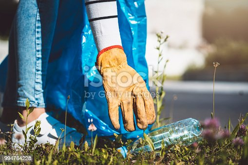 istock Young woman collects plastic bottles and packs in a bag 994764228