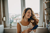 istock Young woman combing hair 1251345644