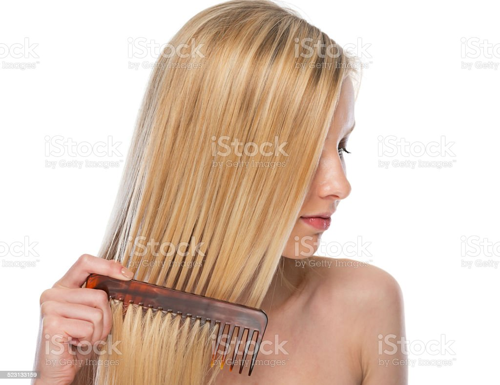 young woman combing hair stock photo