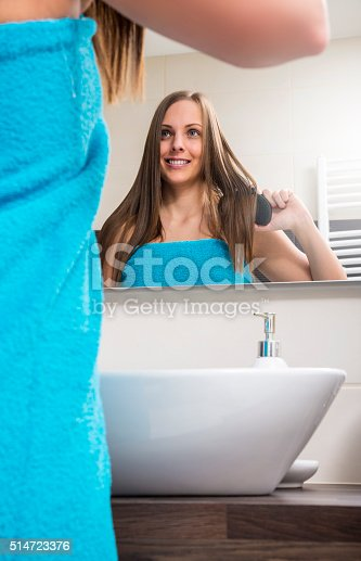 886414246istockphoto Young woman combing her hair 514723376