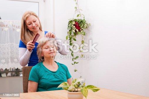 istock young woman combing seniors hair 178547366