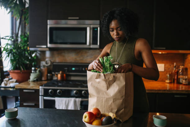 giovane donna torna a casa dalla spesa - grocery home foto e immagini stock