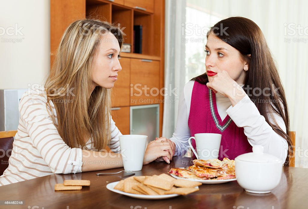 Young woman comforting friend stock photo