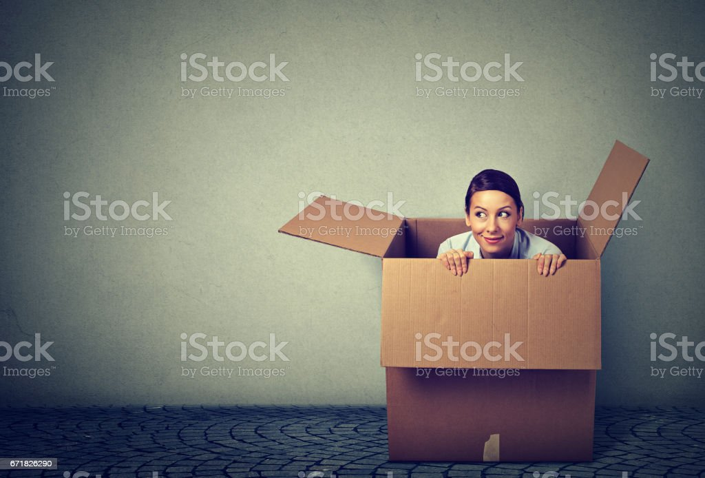 Young woman coming out from a box stock photo