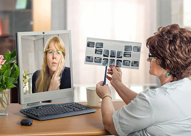 Young woman communicates with dentist in internet stock photo