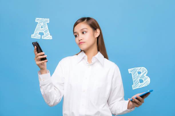 mulher jovem, comparando a de smartphone com smartphone b. - dois objetos - fotografias e filmes do acervo
