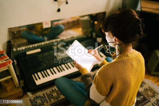Hippie woman sitting on floor and using tablet to create new music