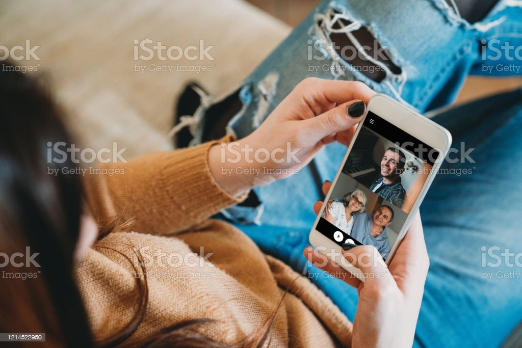 Young woman connecting with her family during quarantine Young woman connecting with her family during quarantine. She's using a smartphone to call her family in Coronavirus COVID-19 time. Accidents and Disasters Stock Photo