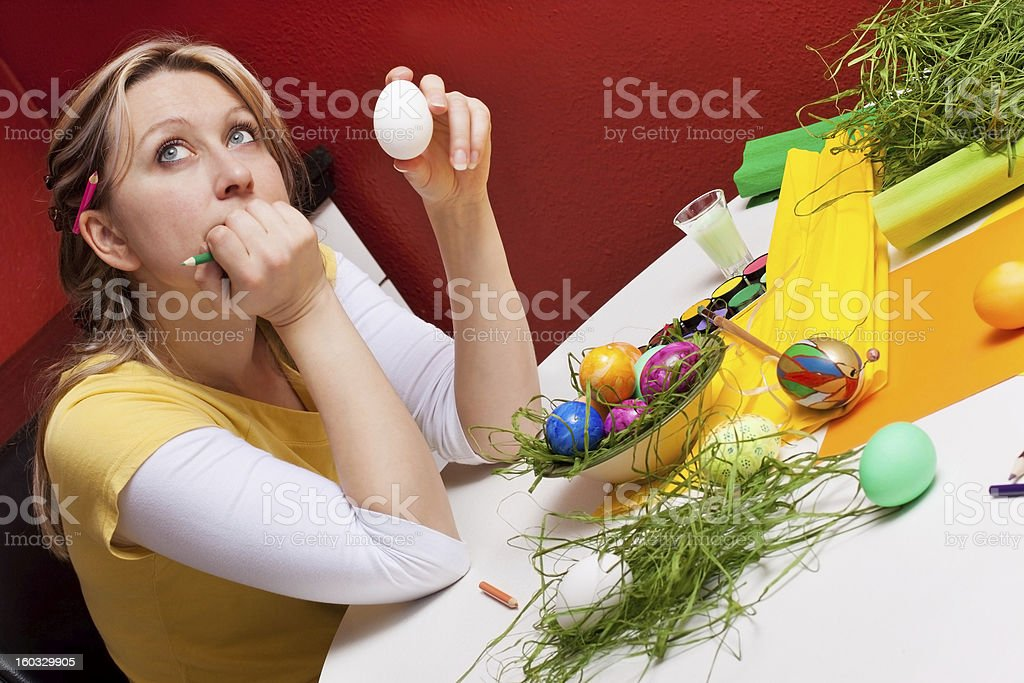 young woman considering how to paint an egg royalty-free stock photo