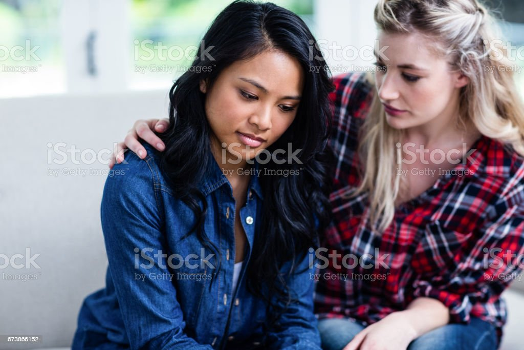 Young woman consoling depressed female friend stock photo