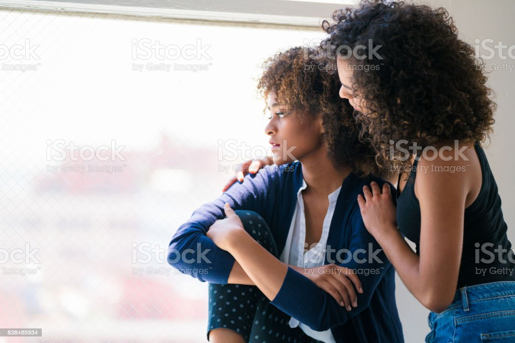 Young woman consoling her friend stock photo