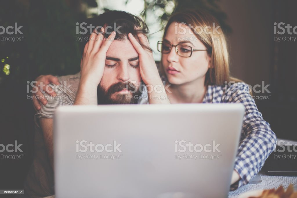 Young woman consoling sad boyfriend and motivate to finish his work foto de stock royalty-free