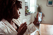 Close up of a young African woman consulting with her doctor over her phone